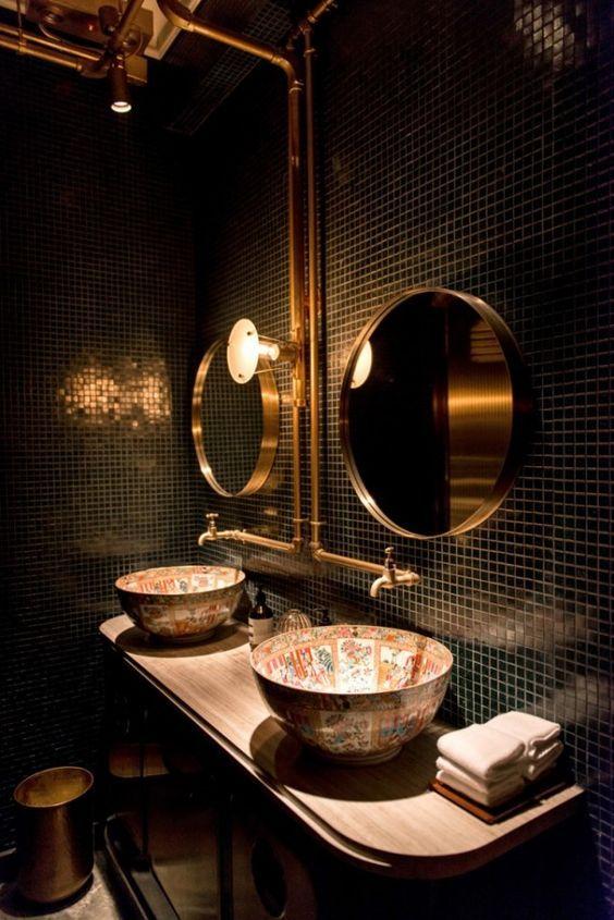 une salle de bains élégante avec des carreaux noirs, des miroirs dorés, des éviers peints et des tuyaux en or exposés est à couper le souffle