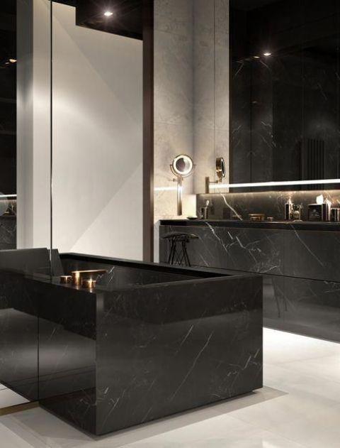une salle de bains élégante avec des murs noirs et blancs, un sol blanc, une baignoire et une coiffeuse en marbre noir ainsi que des miroirs éclairés