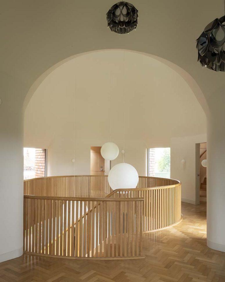 Au premier étage, un salon double hauteur est encadré par la géométrie cintrée de l'intersection de deux cônes