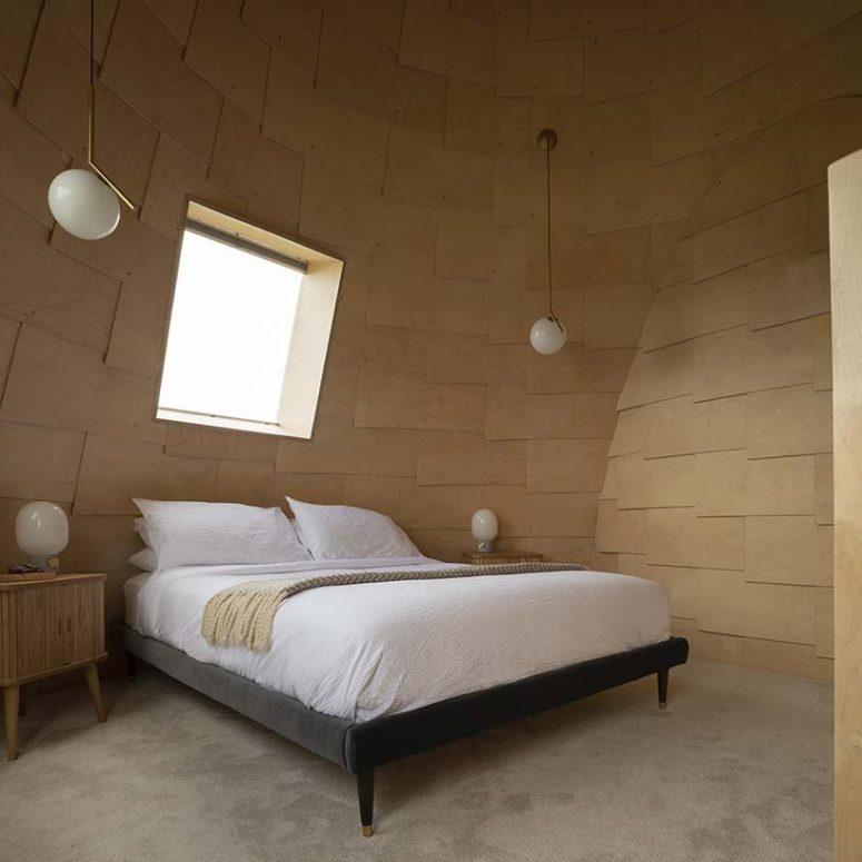 La chambre principale est également recouverte de contreplaqué plié et le mobilier est simple