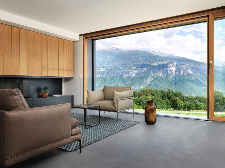 Le salon offre une vue imprenable sur les pistes, il est fait avec des surfaces noires et épurées et du bois, le mobilier est contemporain