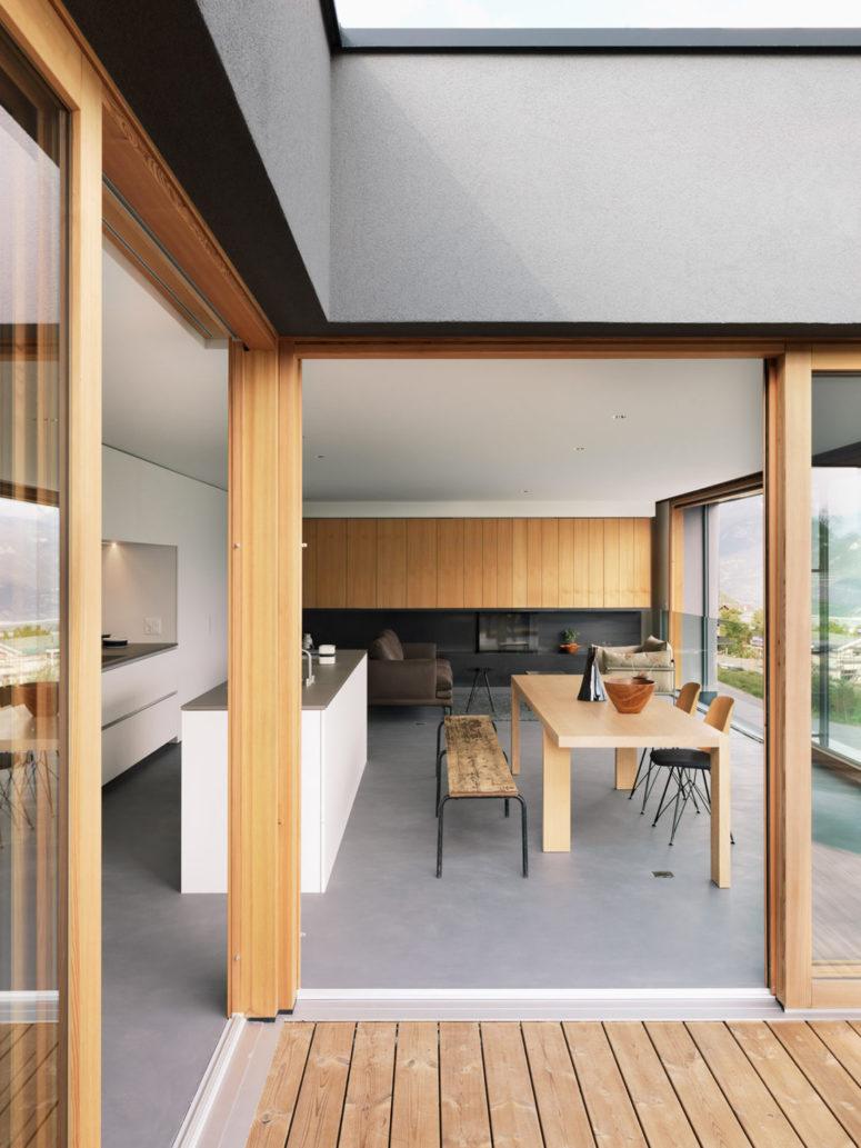 L'espace principal est un aménagement ouvert avec une cuisine minimaliste blanche avec des comptoirs en béton, une salle à manger avec des bancs rustiques et un salon