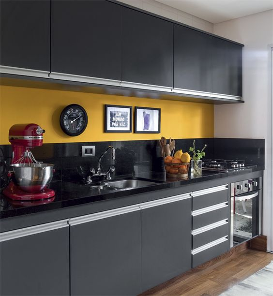 une cuisine audacieuse faite avec des armoires et des comptoirs noirs et un dosseret jaune audacieux semble wow