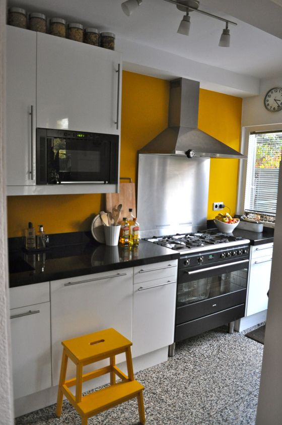 une cuisine lumineuse avec un mur moutarde et un tabouret et tout en noir et blanc pour calmer un peu ça