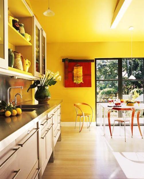 une cuisine jaune vif avec des armoires neutres et des comptoirs noirs ainsi que des œuvres d'art rouges audacieuses semble ultime