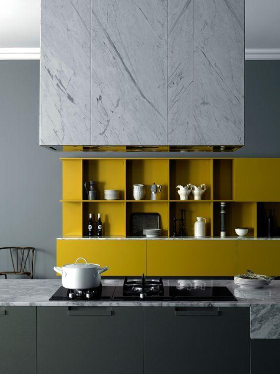 une cuisine minimaliste chic avec un îlot de cuisine noir, des armoires à la moutarde, des touches de marbre blanc sont fantastiques