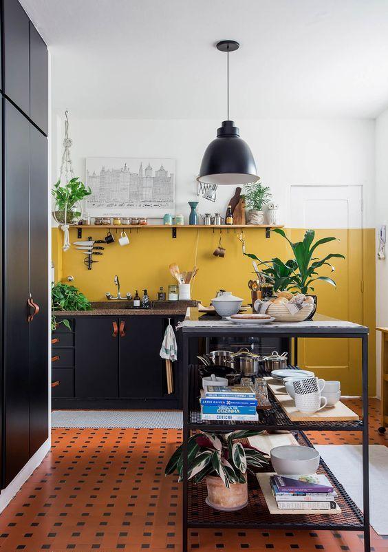 une cuisine contemporaine chic faite avec de la moutarde et des murs blancs, avec des armoires noires, un îlot de cuisine et une lampe noire