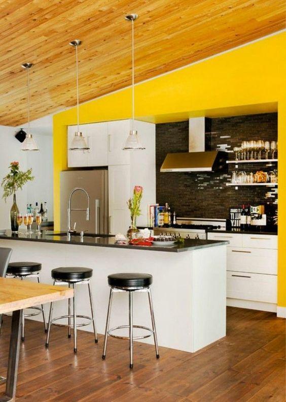 une cuisine lumineuse avec des armoires blanches, des comptoirs noirs et un dosseret, des tabourets noirs et des lampes blanches