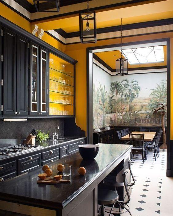 une grande cuisine vintage faite avec des murs jaunes, des armoires noires et des meubles vintage ainsi que des lampes font une déclaration