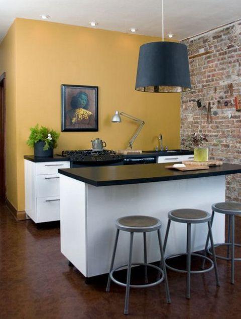 un mini espace cuisine avec un mur jaune foncé, des armoires blanches, des comptoirs noirs, une suspension noire et une œuvre d'art vintage