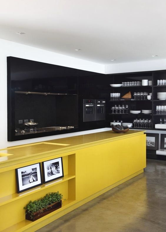 une grande cuisine contemporaine faite avec des armoires et des murs noirs plus un îlot de cuisine jaune vif pour un contraste