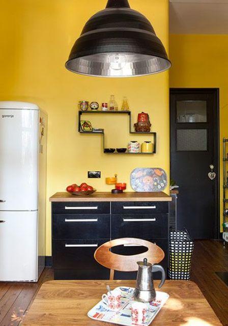 une cuisine moderne du milieu du siècle avec des murs jaunes, des armoires noires, une porte noire et une lampe pour un look affirmé