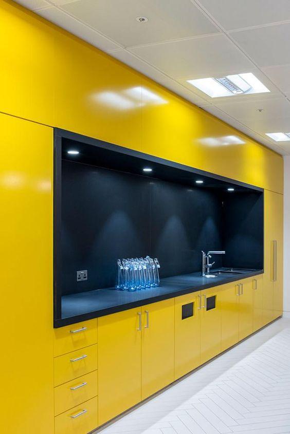 une cuisine jaune minimaliste avec tout ce qui est caché et un grand espace de cuisson noir avec des lumières intégrées est incroyable