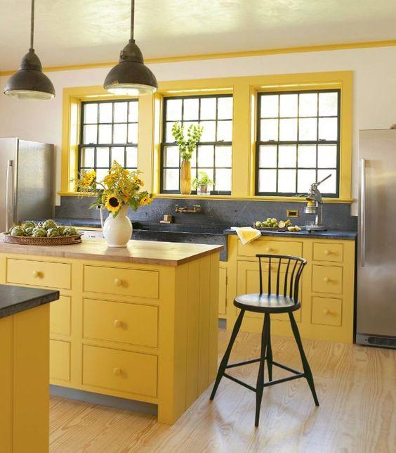 une cuisine jaune ensoleillée avec des suspensions noires, un dosseret et un comptoir noirs ainsi que des chaises noires pour une nouvelle approche du décor traditionnel