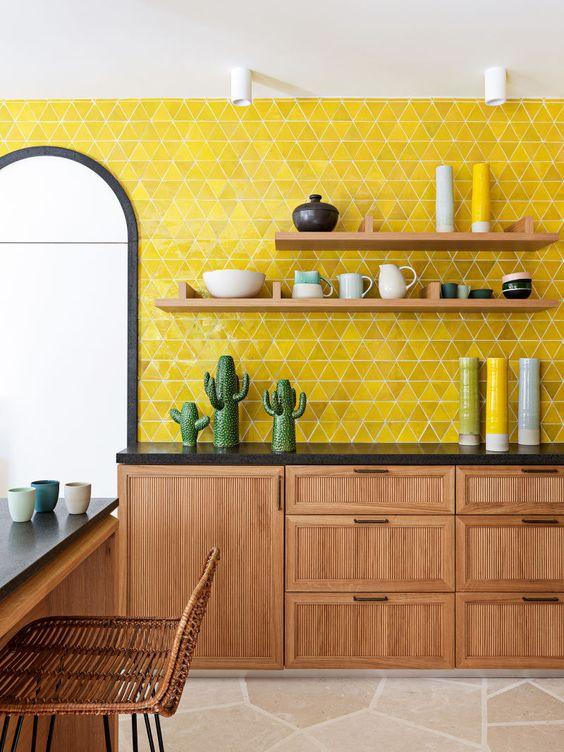 une élégante cuisine moderne du milieu du siècle avec des armoires et des meubles en bois, des comptoirs noirs et un dosseret de carreaux jaune citron