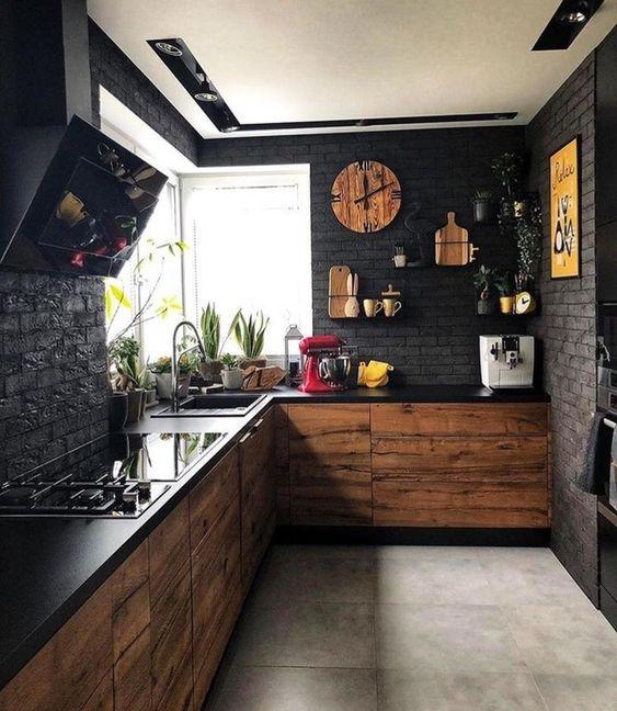 une cuisine noire maussade avec des murs en faux brik, des comptoirs noirs, des armoires en MDF et des touches de jaune