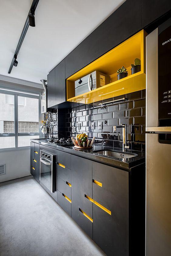 une cuisine noire remarquable avec une étagère jaune vif et des découpes jaunes sur les armoires ainsi qu'un dosseret de carreaux brillants