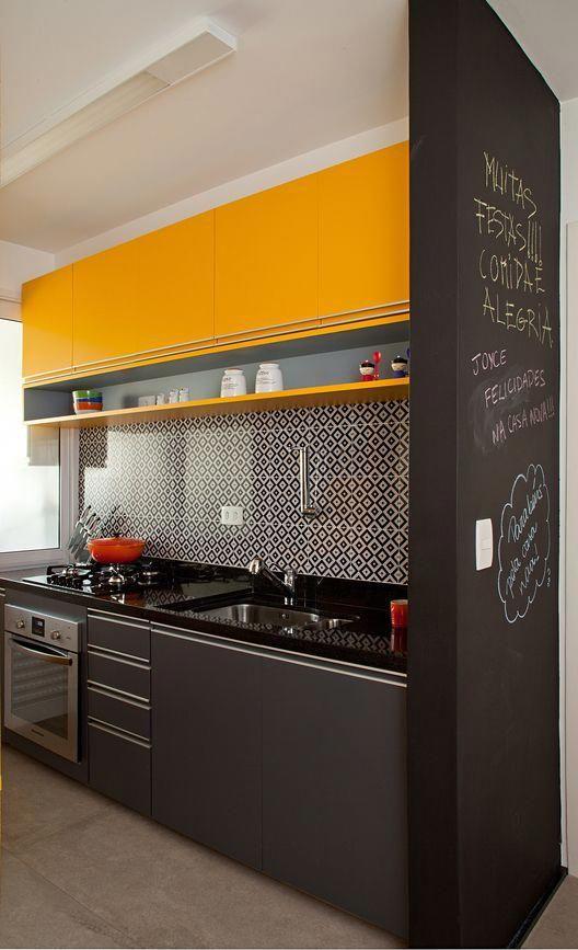 une petite cuisine noire et jaune avec des armoires supérieures lumineuses, des armoires grises inférieures, un dosseret de carreaux de mosaïque et un mur de tableau pour prendre des notes