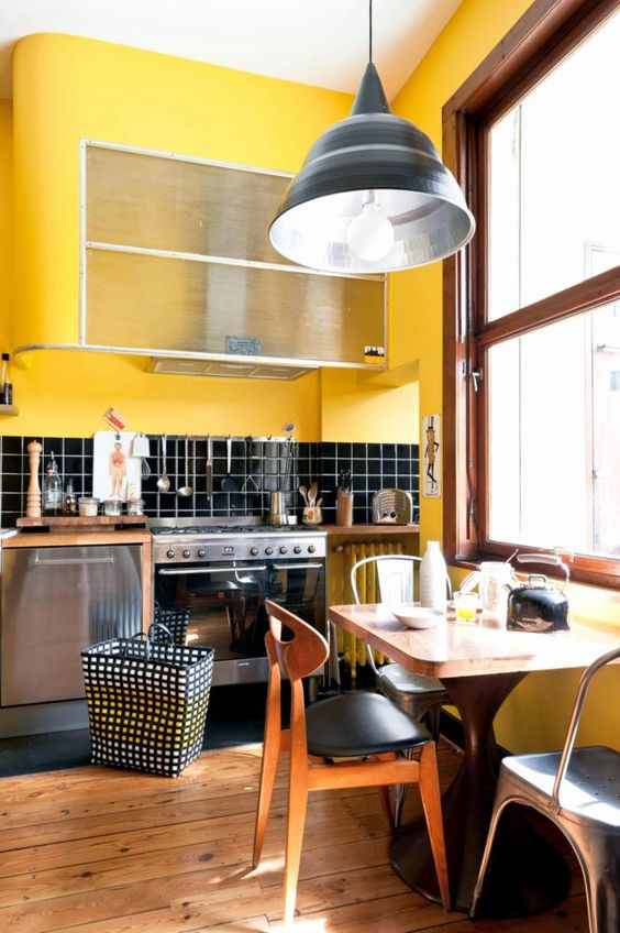 une cuisine rétro faite en jaune vif et noir, avec un mobilier moderne chic du milieu du siècle et des touches de bois teinté chaud
