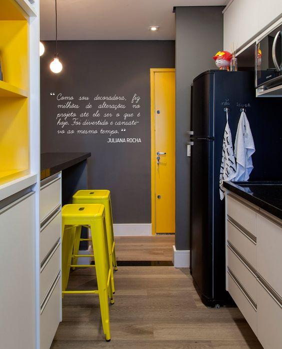 une très petite cuisine noire, blanche et jaune avec un réfrigérateur et des murs noirs, des comptoirs noirs et des touches de différentes nuances jaunes