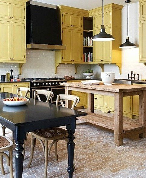 une cuisine vintage faite en noir, jaune pâle et blanc, avec des suspensions et des meubles vintage et rustiques