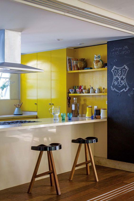 armoires jaune vif, un mur de tableau, des tabourets noirs, un îlot de cuisine encastré blanc pour un look moderne audacieux
