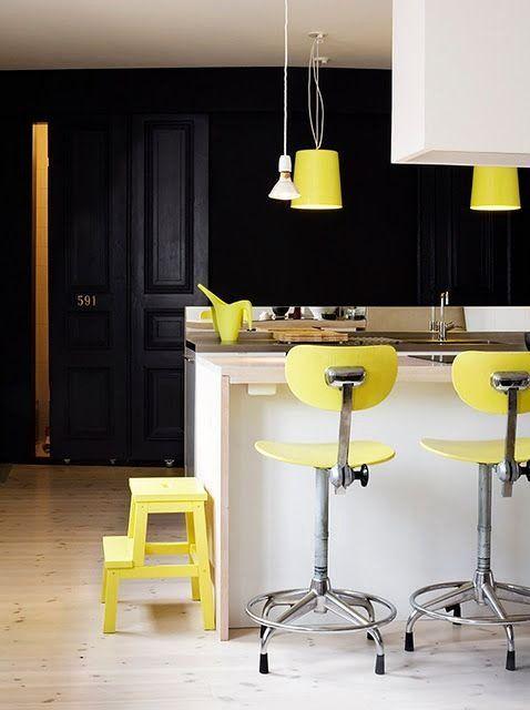 une cuisine moderne super audacieuse avec un îlot de cuisine blanc, une hotte, des armoires noires et des articles jaune citron