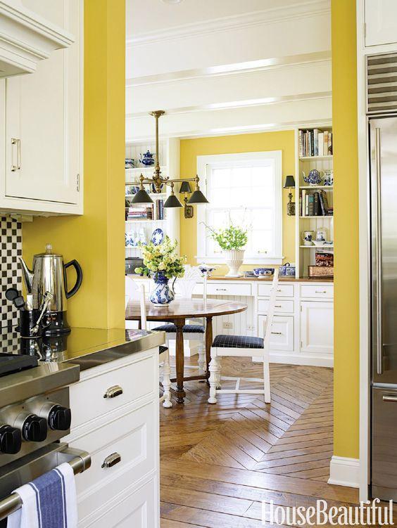 une cuisine vintage avec des murs jaunes ensoleillés, des armoires blanches, des touches de noir et de marine pour un contraste lumineux et des looks audacieux