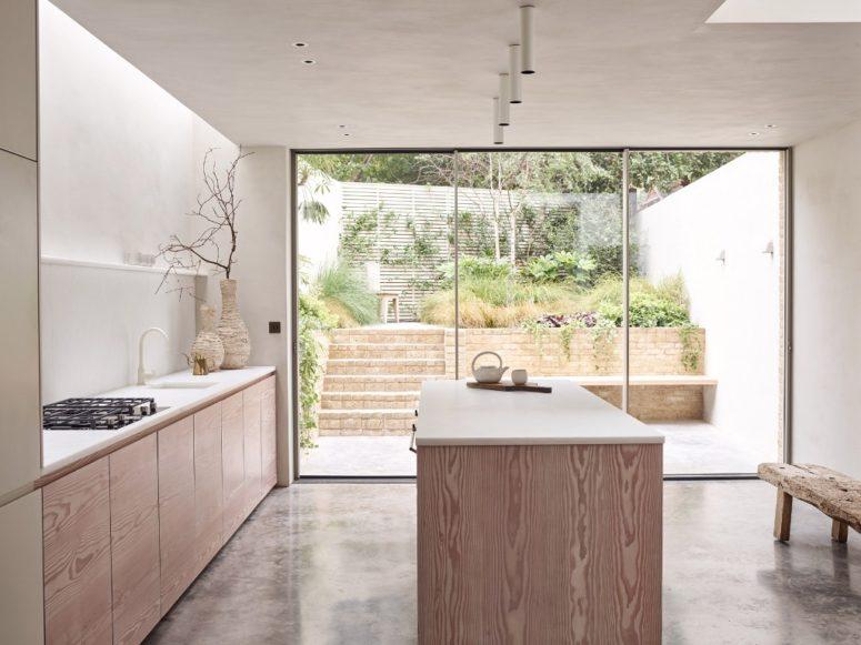 La cuisine est paisible et neutre, les armoires ne sont que des armoires plus basses, de nombreuses surfaces blanches créent une sensation de calme et une porte vitrée apporte beaucoup de lumière naturelle