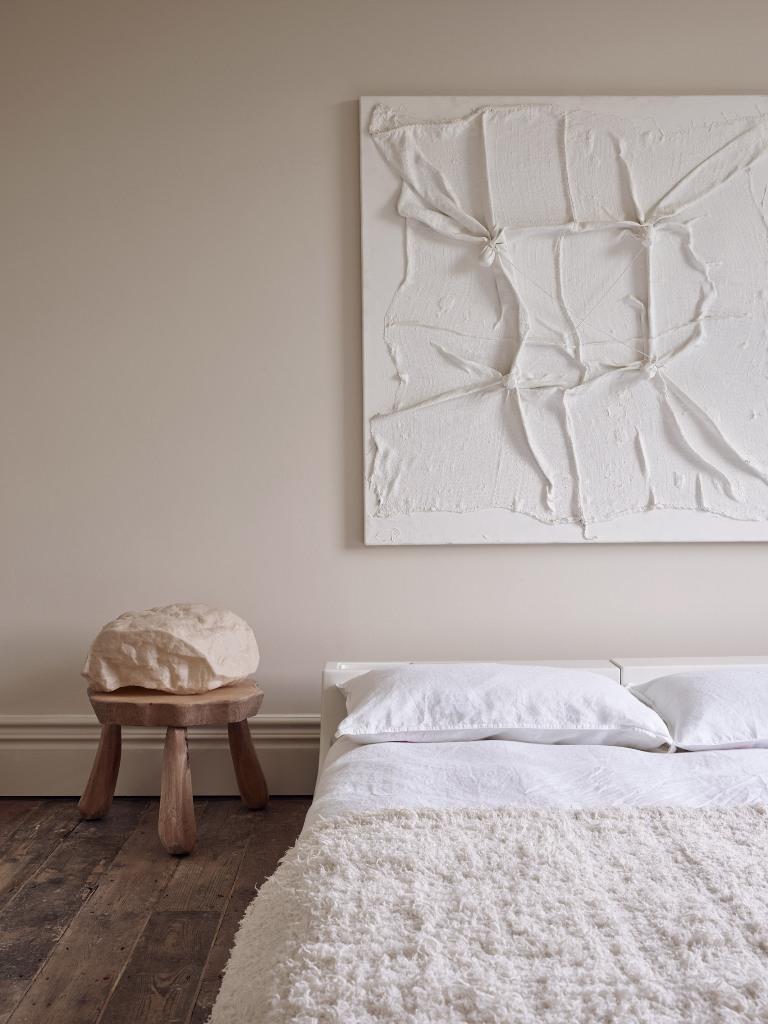 La chambre est faite avec des murs neutres, des meubles simples et une œuvre d'art très accrocheuse