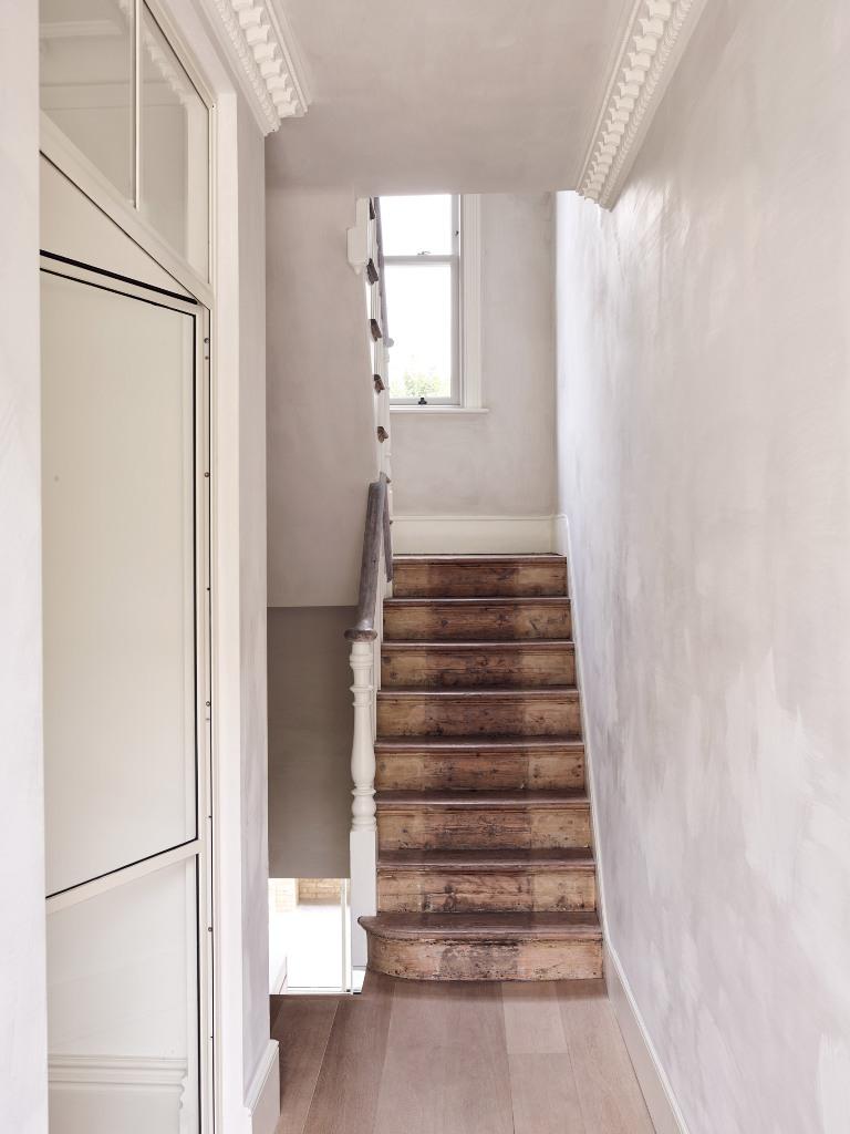 L'escalier est teinté sombre pour faire un contraste avec les murs blancs et ajouter de la texture