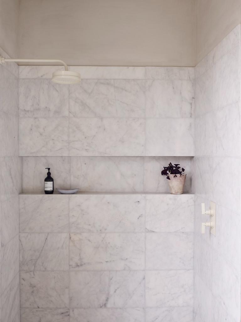 La petite salle de bain dispose d'un espace douche revêtu de carrelage en marbre blanc