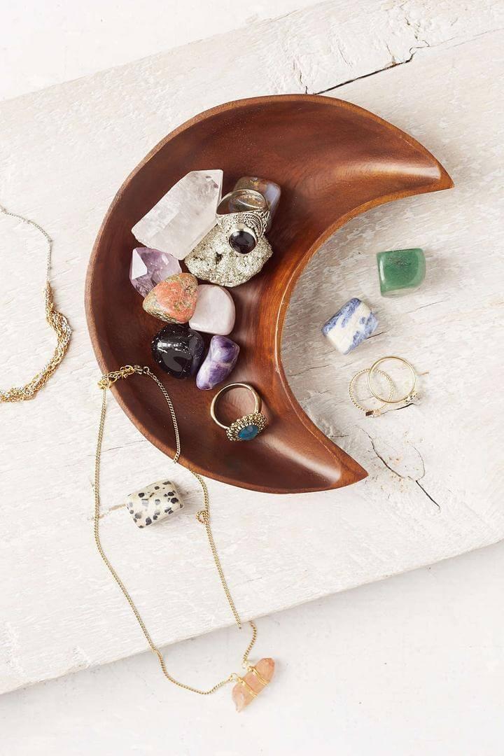 Pierres colorées avec des bijoux dans un bol de lune