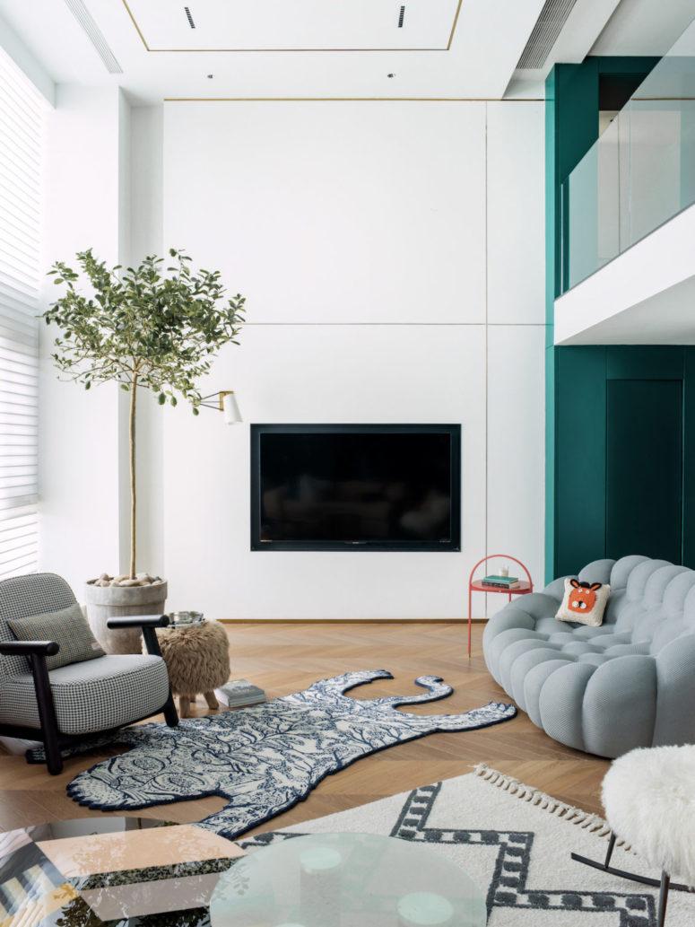 Ceci est une autre pièce sittign, avec un canapé moelleux accrocheur, une télévision intégrée, des tapis superposés et un arbre en pot