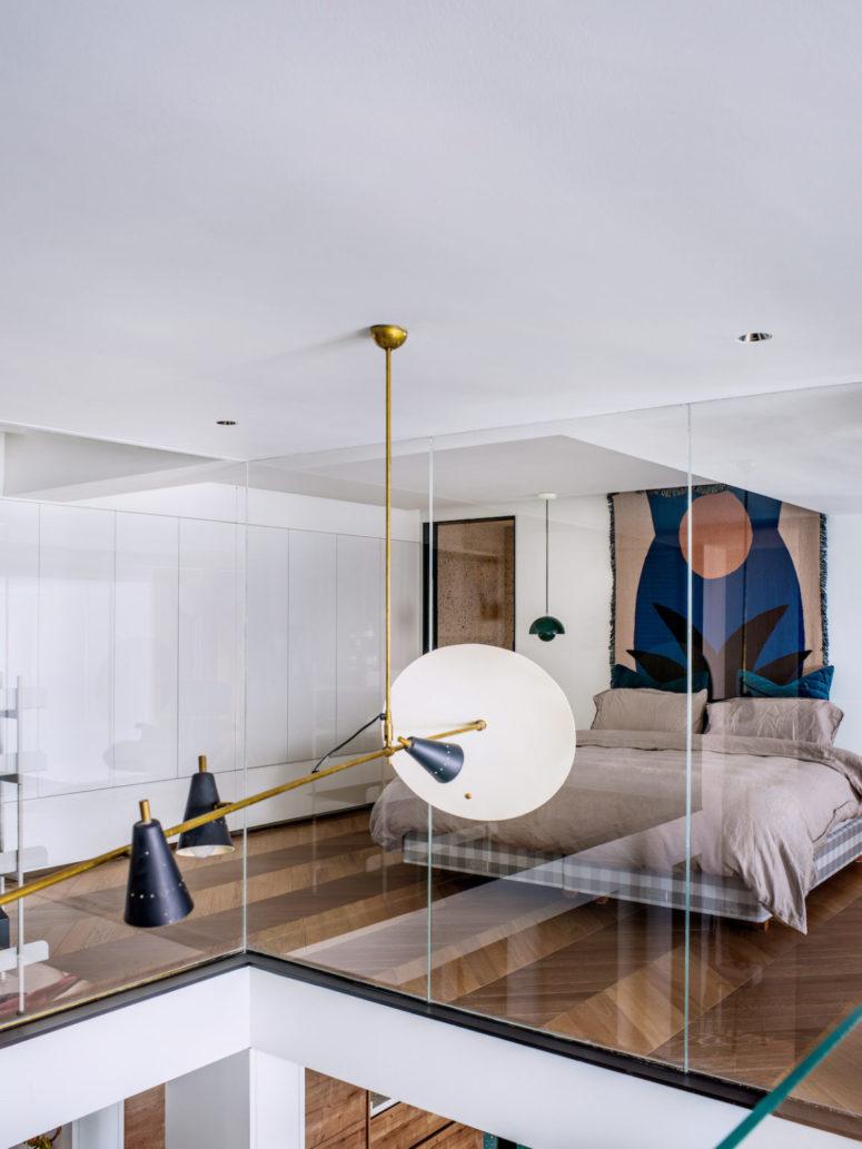 La chambre comprend des unités de rangement fermées et élégantes, un lit flottant, une œuvre d'art lumineuse et des lampes suspendues