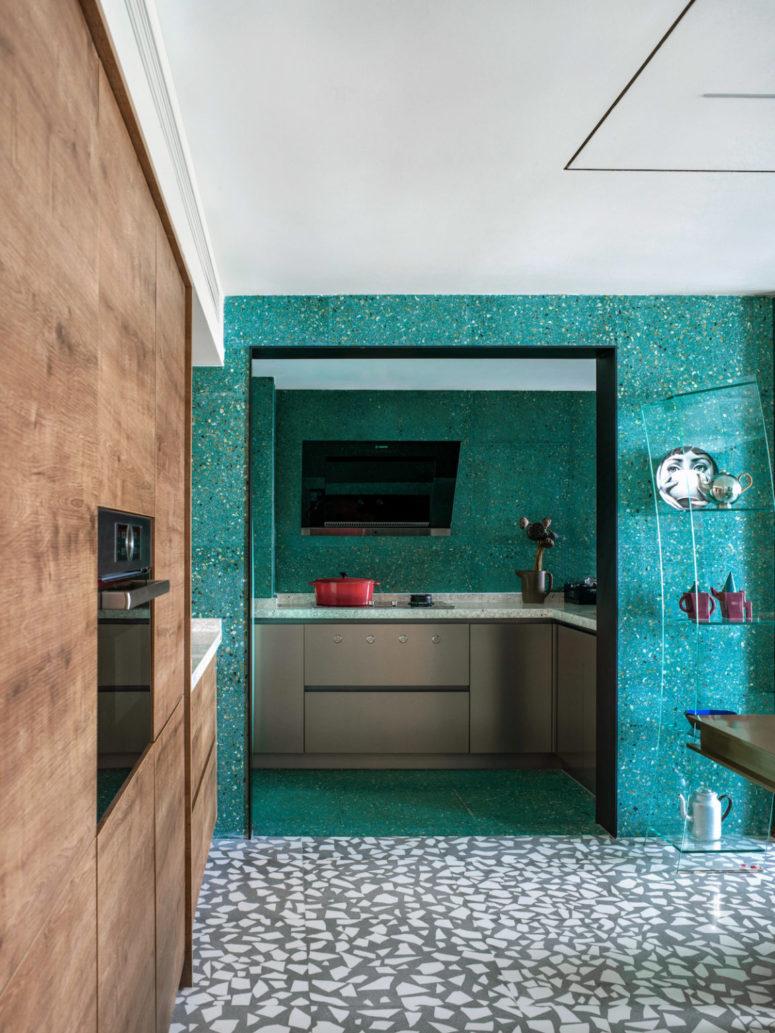 La zone de cuisson est assez petite, avec une télévision et de simples armoires grises avec des comptoirs en terrazzo