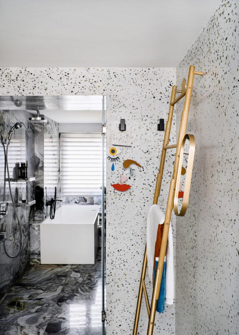 La salle de bain principale est faite de terrazzo et de carreaux de marbre gris, avec des luminaires modernes et des touches d'or