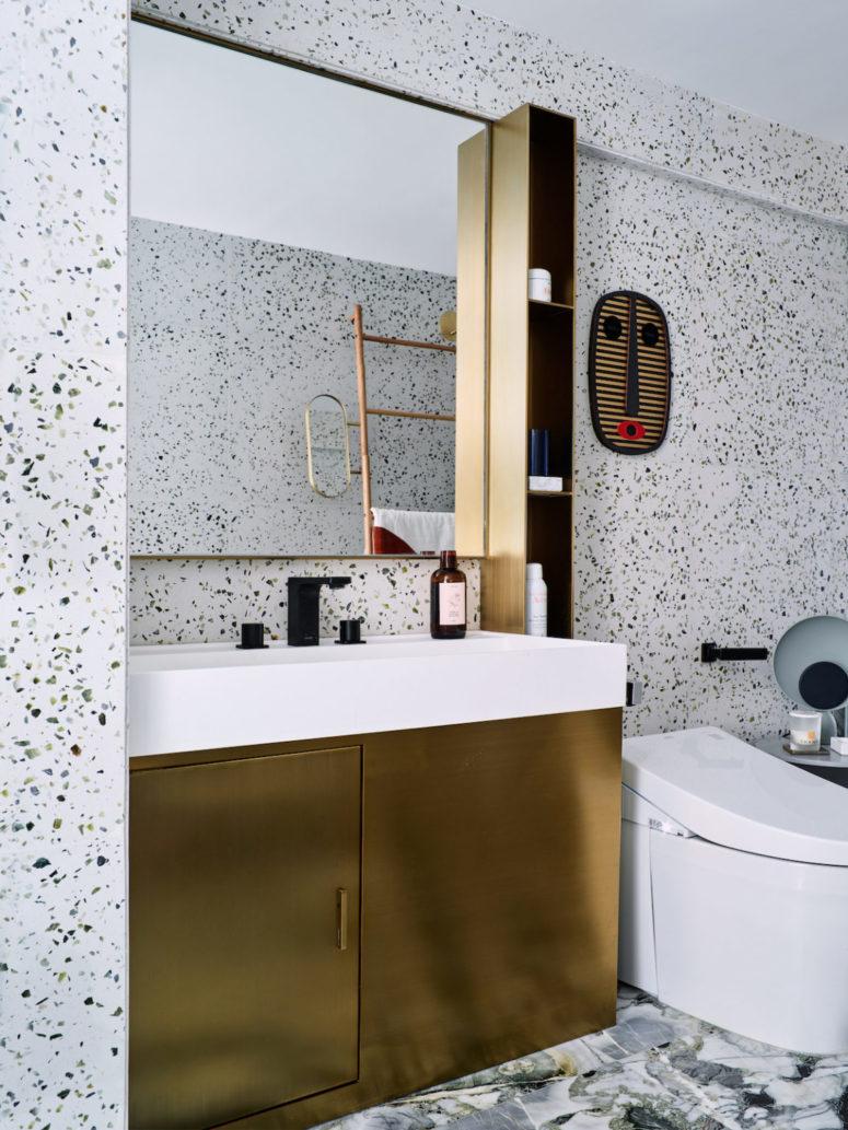 La vanité dorée et une petite étagère ajoutent au look de la salle de bain