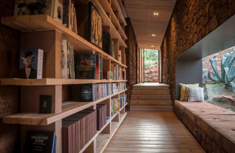 Un couloir est utilisé pour créer un espace de lecture - un wlal est pris par une grande étagère et il y a un espace de lecture au bord de la fenêtre ici