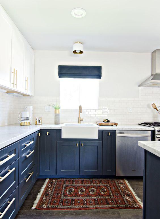 une cuisine audacieuse avec des armoires inférieures bleu marine, des armoires supérieures blanches, des touches dorées, un tapis boho audacieux et des nuances bleu marine