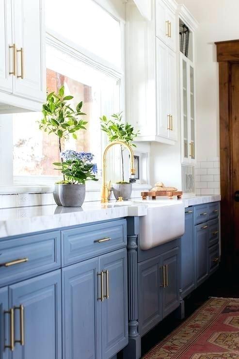 une belle cuisine avec des armoires inférieures bleu clair, des armoires supérieures blanches, des touches dorées et des fleurs en pot