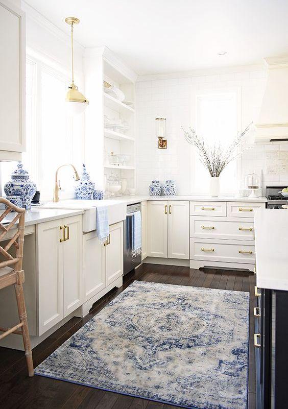 une cuisine neutre chic agrémentée d'un tapis bleu et d'un peu de porcelaine et de touches d'or pour plus de chic