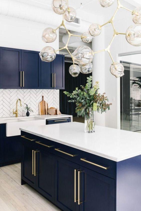 une cuisine audacieuse et chic avec des armoires bleu marine, des comptoirs blancs et un dosseret et un lustre accrocheur avec des touches dorées