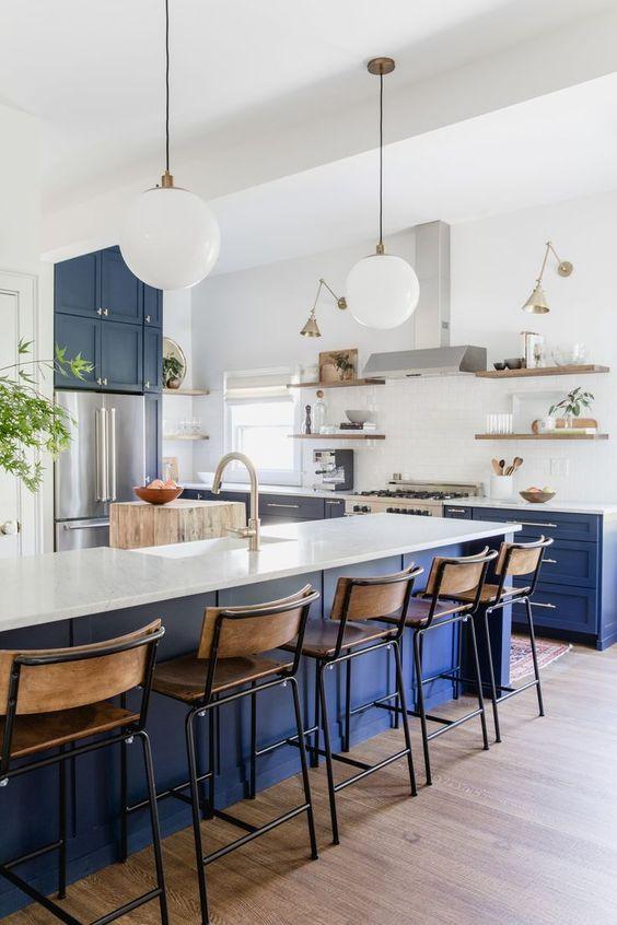 une cuisine moderne et lumineuse avec des armoires inférieures bleues audacieuses et un îlot de cuisine, des comptoirs blancs et un dosseret