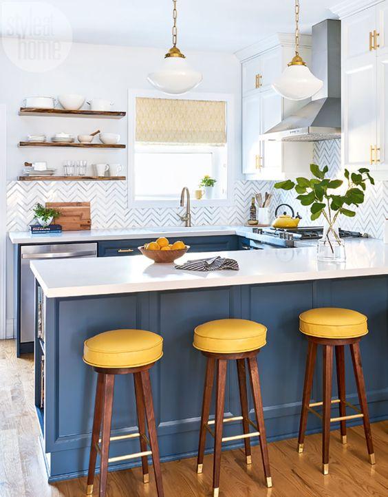 une cuisine lumineuse avec des armoires bleu marine, des comptoirs blancs et un dosseret à chevrons plus des touches de laiton et d'or