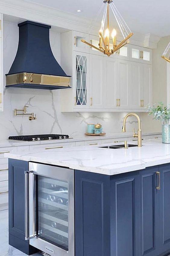 une cuisine lumineuse avec des armoires blanches, un îlot de cuisine bleu et une hotte et beaucoup d'or pour rendre l'espace exquis