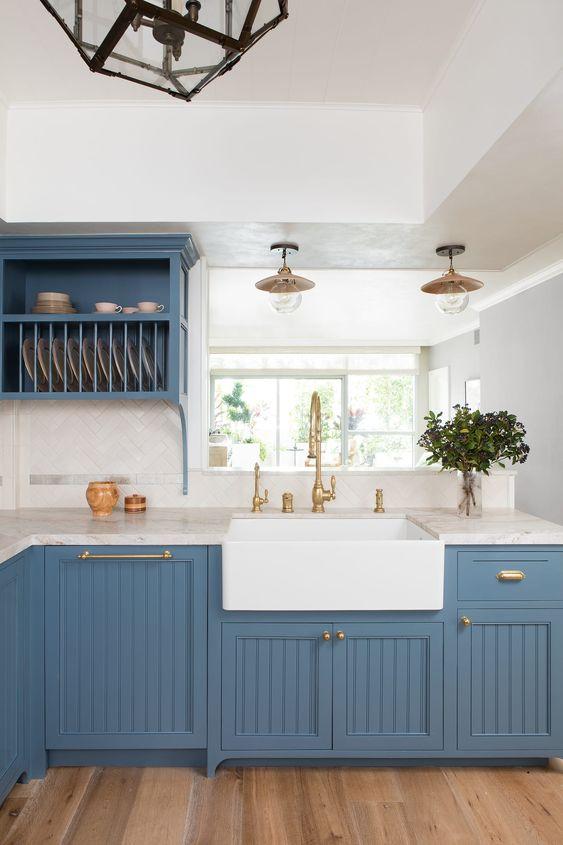une cuisine pimpante en bleu rafraîchi avec des comptoirs en pierre blanche et un dosseret de carreaux blancs plus de l'or