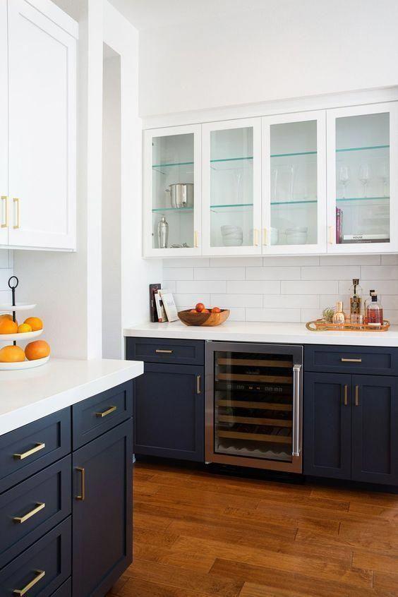 une cuisine contrastée avec des armoires inférieures bleu marine, des armoires supérieures blanches, des dosserets de carreaux blancs et des comptoirs blancs