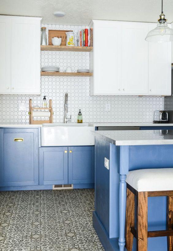 une cuisine contemporaine avec des armoires inférieures bleu clair et des armoires supérieures blanches plus des touches d'or