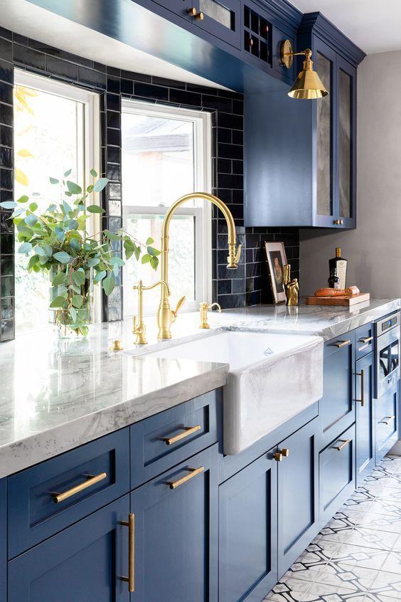 une superbe cuisine traditionnelle en bleu, avec des comptoirs en pierre blanche, un dosseret de carreaux noirs et des touches dorées